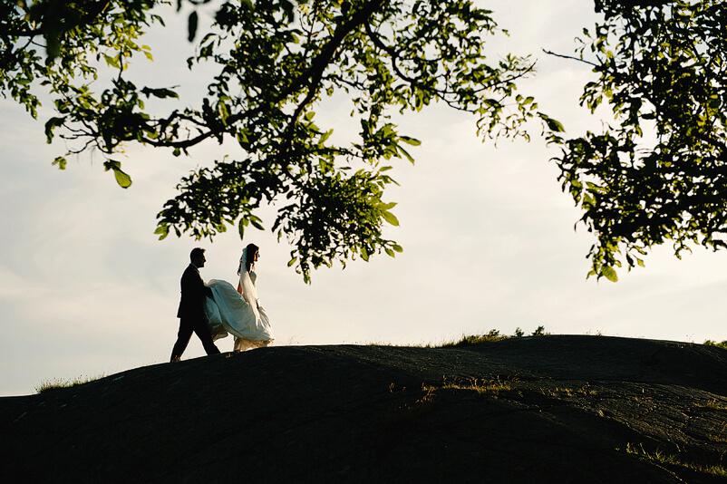 Brudgummen håller upp brudens släp när de går över klipporna vid Tjolöholms slott.