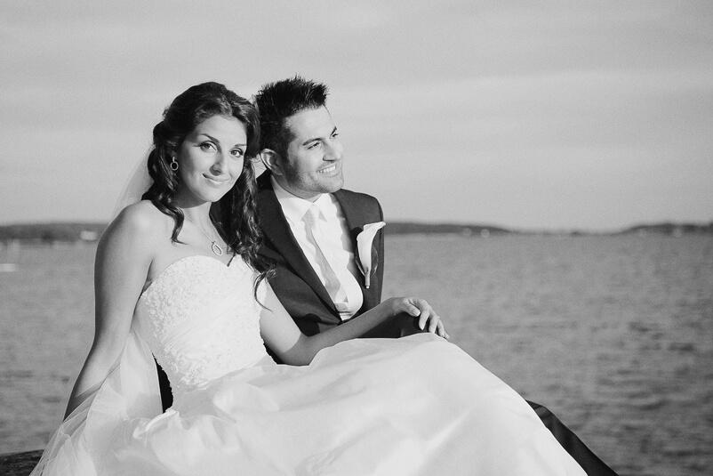 Bruden ler och ser in in i kameran med brudgummen vid sin sida och havet som bakgrund vid Tjolöholms slott.