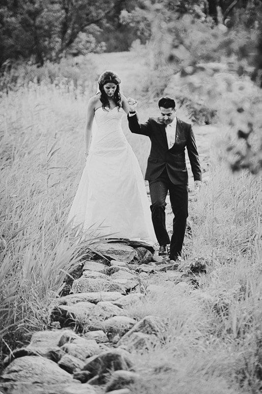 Brudparet vandrar mot betraktaren längs stengärdsgården vid Storeskog på Tjolöholms slott.